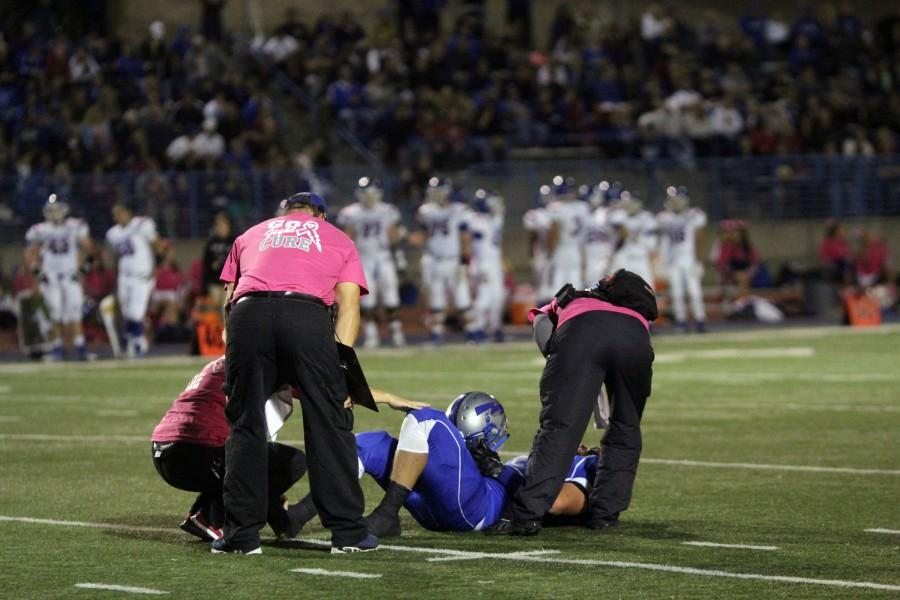 Senior Justin Edgecomb being examined by trainers after being injured against Folsom