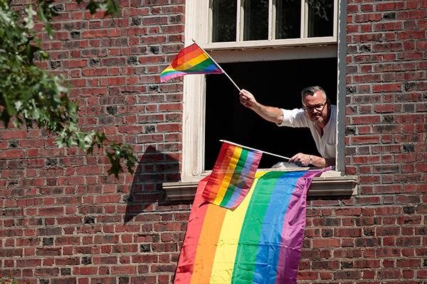 NEW YORK, NY - JUNE 26: A man leans out his window on 5th Avenue to watch the New York City Pride March, June 26, 2016 in New York City. This year was the 46th Pride march in New York City. (Photo by Drew Angerer/Getty Images)