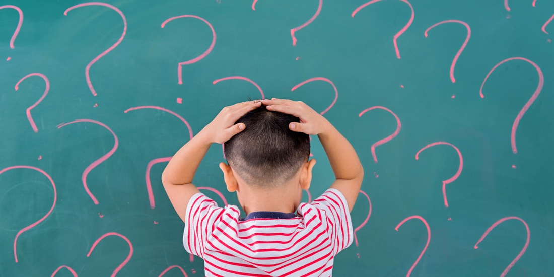Asian little boy in front of blackboard with question marks.